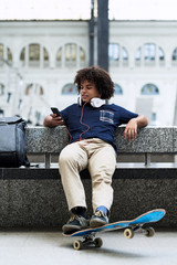 Teenager using cell phone with headphones sitting on bench with skateboard.