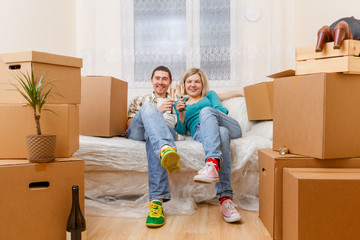 Photo of couple sitting on couch and drinking shampagne among cardboard boxes