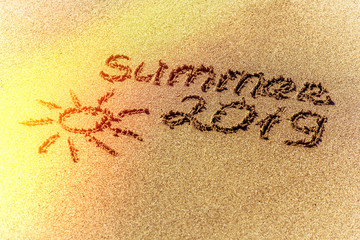 The word summer and sun written in the sand on a beach