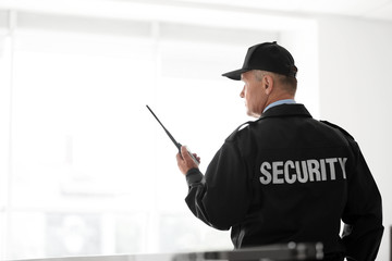 Male security guard using portable radio transmitter on light background
