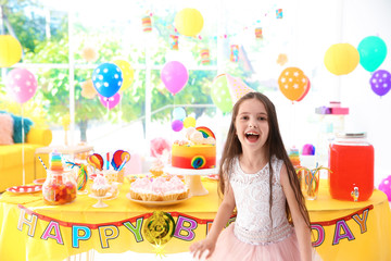 Cute little girl near table with treats at birthday party indoors