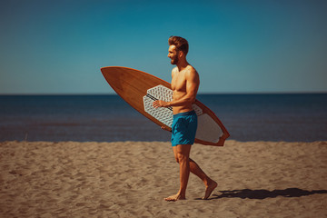 Young man with a surf board on the beach