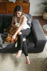 Young hanging out on woman on couch with dog