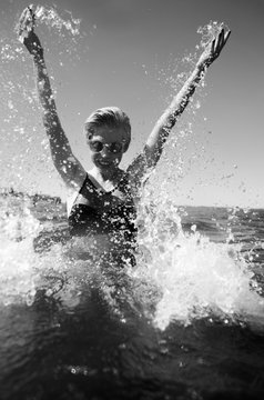 happy young female play with water splashes