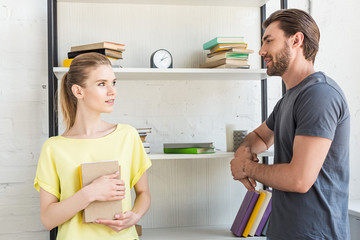 young attractive woman holding book and talking to smiling boyfriend near shelves with books