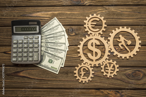 Calculator American Dollar Banknotes Of Currency Signs Businessman Runs In Gears On A Wooden
