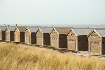 Wooden houses and dry grass on the beach.