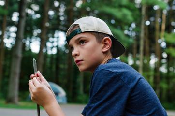 A Boy Sharpening a Stick