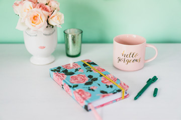 Feminine desk with notebook, coffee, and flowers
