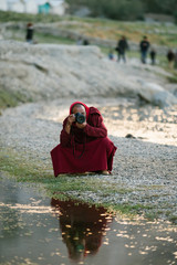 Anonymous Buddhist monk squating and taking picture of river