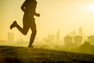 Defocused silhouette of jogger running on a green grassy hill in front of the misty London city skyline. Focus on buildings in the background.