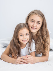 portrait of mother and daughter hugging on the bed
