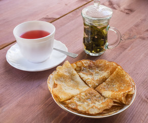 Plate with pancakes, a cup of tea on a wooden table