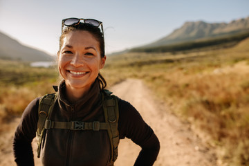 Smiling asian woman with backpack on country hike