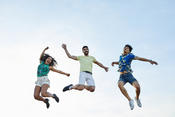 Happy friends jumping over sky.