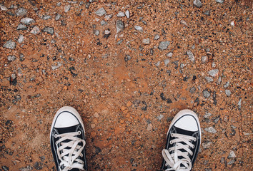 Sneakers on the gravel. Copy space. Walking on foot. Modern comfort.