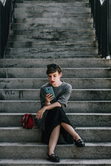 Young woman with mobile phone sitting on the stairs.