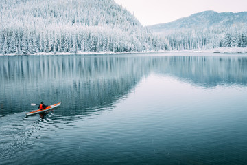 A solo kayaker paddles on a still lake one quiet winter morning in Montana