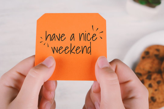 """Woman hands holding note paper with text """"have a nice weekend"""""""
