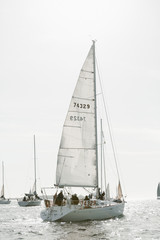 white sailboat at sea in yacht race with crew on board