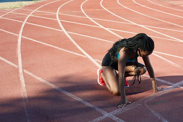 African young woman athlete positioning to start a run in the track and field
