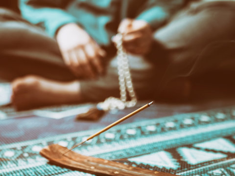 Concentrated woman praying with wooden rosary mala beads. Close up, focus on incense stick. Retro vintage filter.