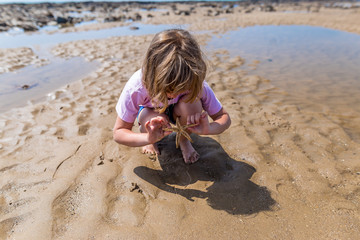 Girl with the starfish on low tide at seaside