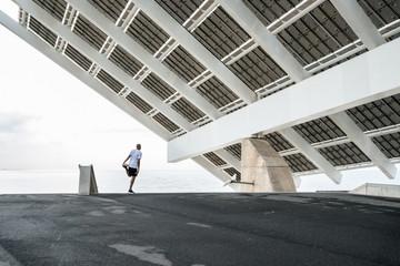 Man stretching on waterfront