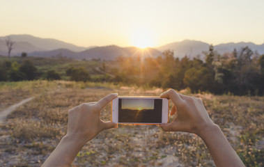 Female hiker photographing a sunset landscape with her phone cam