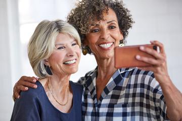 Senior women doing a selfie photo in kitchen