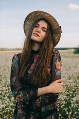 Front view portrait of young fashionable woman in black dress with floral print and straw hat looking at camera