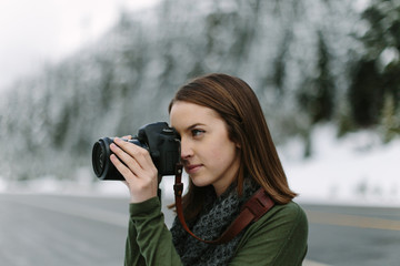 Woman Taking Picture of Winter Landscape