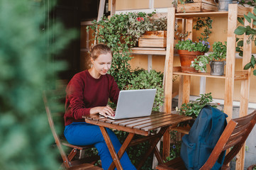 Young woman working on laptop in outdoors cafe