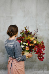 Woman holding bunch of rustic flowers