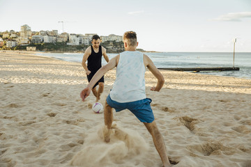 Male Friends Playing Soccer on the Beach