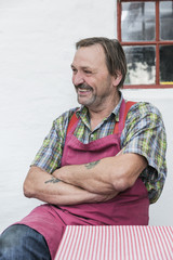 Senior man in red apron on a break laughing