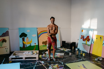 An artist painter in front of his paintings