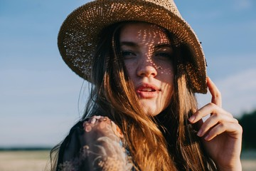 Fashionable portrait of pretty female wearing straw hat in warm summer day and shadows on her face