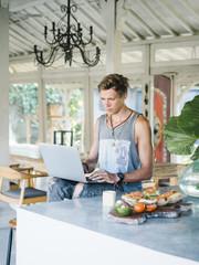 Man sitting at counter wiht laptop