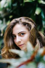 Young woman among green plants