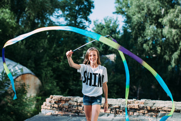 Lovely girl wearing t-shirt with word Shine playing with sportive ribbon outdoors and smiling at camera