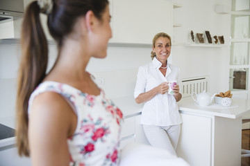 Smiling mother talking to her daughter in the kitchen