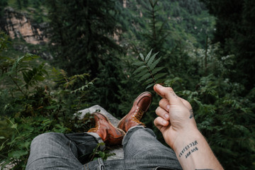 Anonymous man in a leather boots lying in jungle while holding fern stalk with tattooed hand