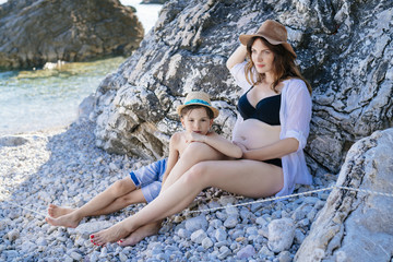 A pregnant mother and her son on the beach by the sea