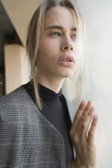 Portrait of a beautiful blond girl near the window