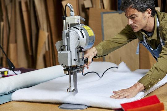 Worker Using Fabric Cutting Machinery In Sofa Workshop