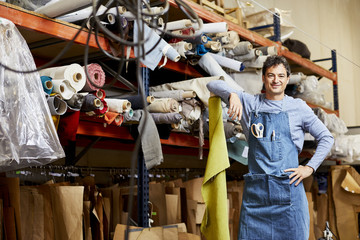 Confident Worker Leaning On Rolled Up Fabric In Sofa Workshop
