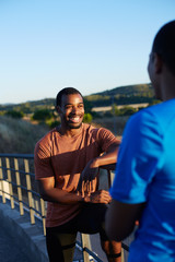 Two african american friends wearing sports clothes in a relax moment of their workout chatting outdoors