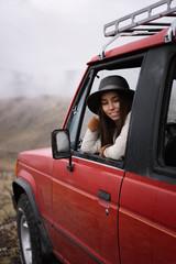 Content traveler posing in car