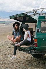 Two young tattooed women resting while sitting on old jeep, parked in the wild area